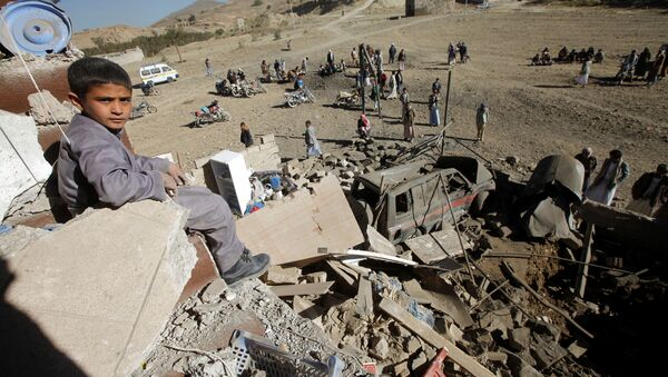 A boy looks at the camera as he sits on the wreckage of a house destroyed by a Saudi-led air strike on the outskirts of Sanaa, Yemen, November 13, 2016 - Sputnik International