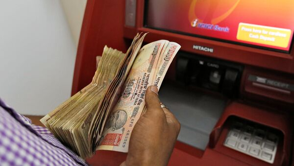 A customer deposits 1000 and 500 Indian rupee banknotes in a cash deposit machine at bank in Mumbai, India, November 8, 2016 - Sputnik International