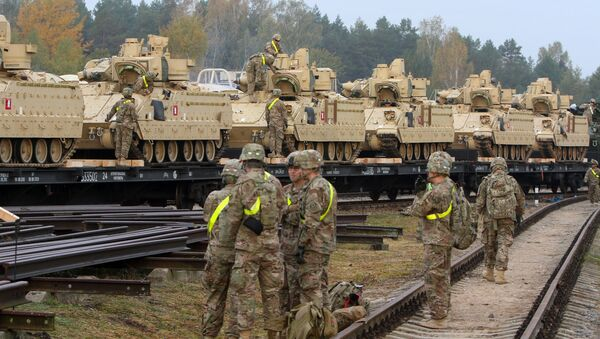 Members of the US Army 1st Brigade, 1st Cavalry Division, unload heavy combat equipment including Bradley Fighting Vehicles at the railway station near the Rukla military base in Lithuania, on October 4, 2014 - Sputnik International