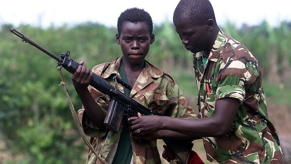 A fourteen year old child soldier for the Sierra Leone Army, Abu Kamara, left, is helped with his British self Loading rifle (SLR) by another soldier while protecting the small town of Ropath near Masiaka, 55 km east of the capital Freetown, Tuesday May 23, 2000 - Sputnik International