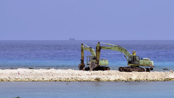 Two excavators are pictured at a construction site on Taiping island in the Spratly chain in the South China Sea on March 23, 2016 - Sputnik International