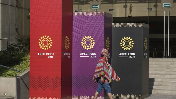 A man dressed in traditional Andean clothes walks past the logo of the APEC 2016 summit in Lima, Peru, Wednesday, Nov. 16, 2016 - Sputnik International
