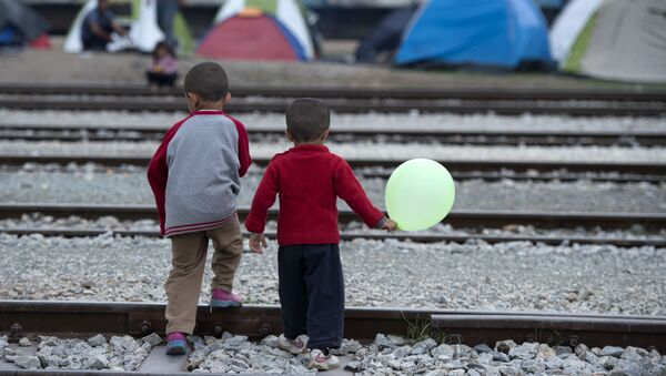 Children cross rail tracks at a makeshift camp for migrants and refugees near the village of Idomeni not far from the Greek-Macedonian border - Sputnik International