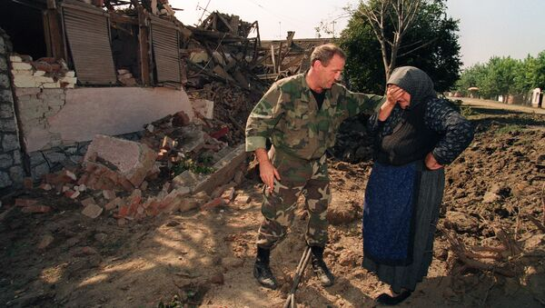 A Croatian National Guardsman comforts an old woman on September 26, 1991, outside her home which was destroyed in an air raid during the night by Yugoslav Serbian Federal air forces - Sputnik International