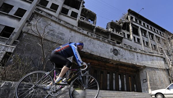 A man rides his bike on March 22, 2009 past the building of the former federal Interior Ministry in Belgrade, which was destroyed during the 1999 NATO air campaign against Serbia and Montenegro - Sputnik International