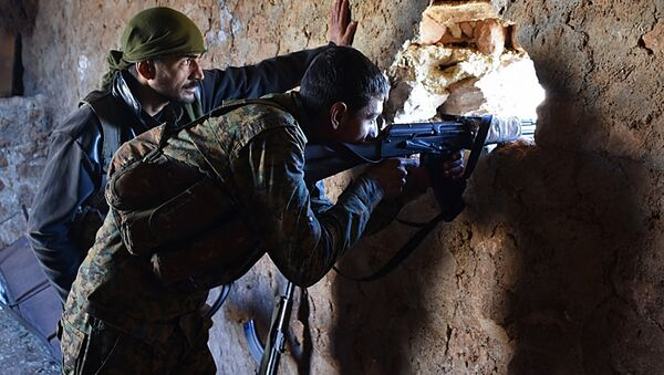 A fighter from the Syrian pro-government forces mans a riffle inside a damaged house in the recently recaptured village of Joubah during an offensive towards the area of Al-Bab in Aleppo province, on November 25, 2016 - Sputnik International