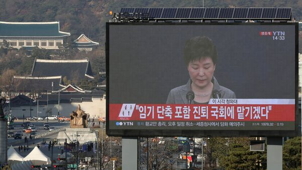 A large electronic board broadcasts a news report on South Korean President Park Geun-hye releasing a statement to the public as the Presidential Blue House (top L) is seen in the background, in central Seoul, South Korea, November 29, 2016. - Sputnik International
