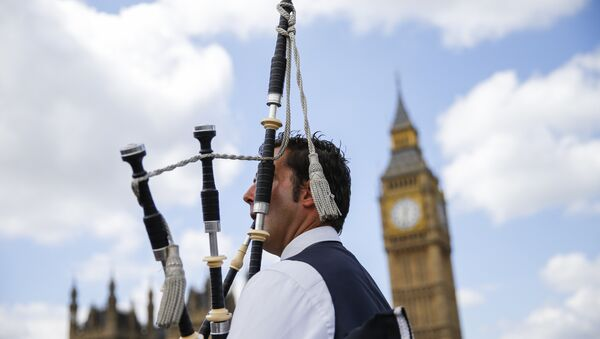 A Scottish piper plays for tourists in front of the Queen Elizabeth Tower (Big Ben) and The Houses of Parliament in central London on June 26, 2016. - Sputnik International