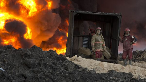 Fire fighters work to quell an oil fire set by Islamic State militants in Qayara, south of Mosul, Iraq, Monday, Nov. 28, 2016.  - Sputnik International