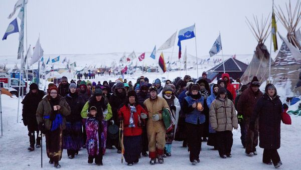 In this Thursday, Dec. 1, 2016 photo, Beatrice Menase Kwe Jackson, center, walks with Daniel Emory, both of the Ojibwe Native American tribe as they lead a procession to the Cannonball river for a traditional water ceremony at the Oceti Sakowin camp where people have gathered to protest the Dakota Access oil pipeline in Cannon Ball, N.D. - Sputnik International