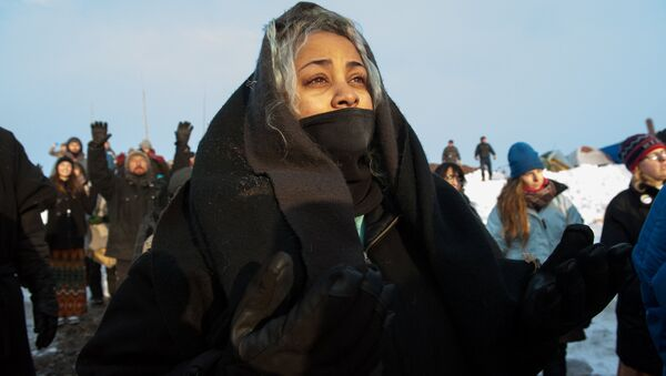 A woman watches the sunrise in Oceti Sakowin camp as water protectors continue to demonstrate against plans to pass the Dakota Access pipeline near the Standing Rock Indian Reservation, near Cannon Ball, North Dakota, U.S. December 3, 2016 - Sputnik International