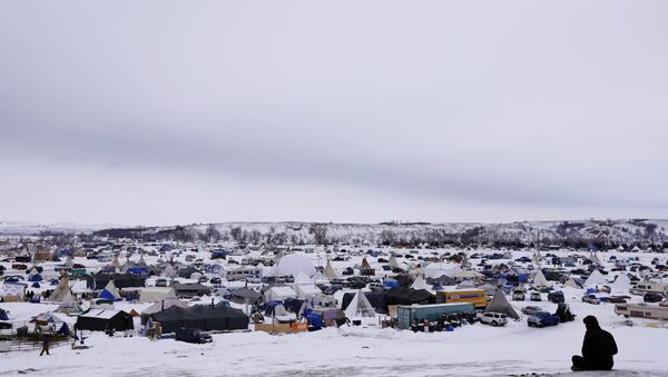 A man rests on top of a hill inside of the Oceti Sakowin camp as water protectors continue to demonstrate against plans to pass the Dakota Access pipeline near the Standing Rock Indian Reservation, near Cannon Ball, North Dakota, U.S., December 2, 2016 - Sputnik International