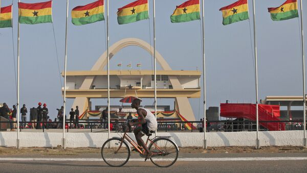 A man rides a bicycle past Ghanian flags flown at half mast to honor late Ghanian President, John Evans Atta Mills at the independence square in Accra, Ghana, Thursday, Aug.9, 2012. - Sputnik International