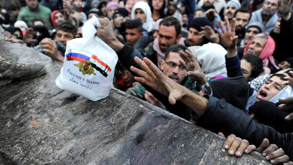Syrians who have been evacuated from eastern Aleppo, reach out for Russian food aid in government-controlled Jibreen area in Aleppo, Syria November 30, 2016. The text on the bag, which shows the Syrian and Russian national flags, reads in Arabic: Russia is with you. - Sputnik International