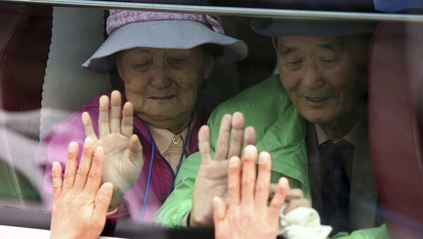 South Koreans on a bus touch the bus window in their attempt to feel hands of their North Korean relatives as they bid farewell after the Separated Family Reunion Meeting at Diamond Mountain resort in North Korea. (File) - Sputnik International