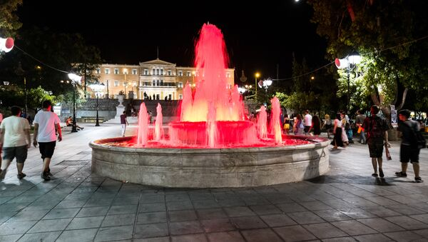 People walk near the fountain at Syntagma Square in front of the Greek Parliament in central Athens on July 4, 2015. - Sputnik International