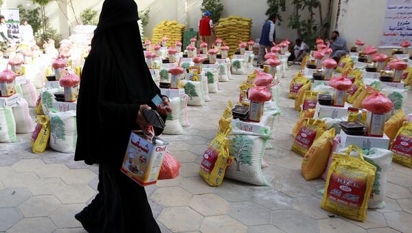 A Yemeni woman affected by the country's ongoing conflict walks past food rations provided by an initiative organised by a local charity in the capital Sanaa on June 2, 2016. - Sputnik International