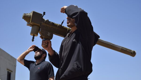 Rebel-fighters monitor the sky holding a man-portable air-defence system (MANPADS) in the Syrian village of Teir Maalah, on the northern outskirts of Homs, on April 20, 2016. - Sputnik International
