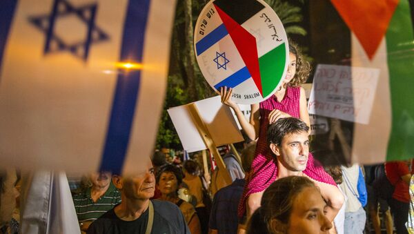 A young girl holds a bearing images of the Israeli and Palestinian flags during a Israeli left-wing activist rally demanding fresh Israeli-Palestinian peace talks, on the eve of the 20th anniversary of the killing of late Israeli prime minister Yitzhak Rabin, at the Rabin Square in the Israeli city of Tel Aviv on October 24, 2015 - Sputnik International