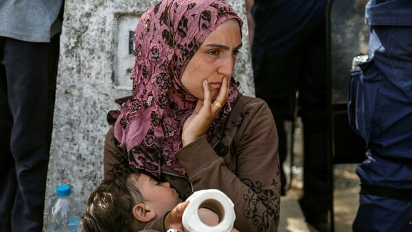 A woman sits with her child after migrants and refugees tried to open the border fence at a makeshift camp at the Greek-Macedonian border near the village of Idomeni, Greece, April 7, 2016. - Sputnik International