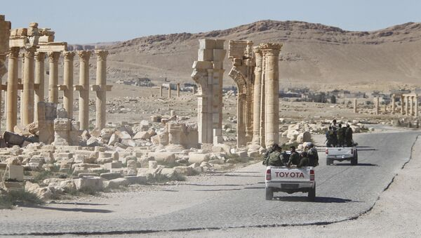 Syrian army soldiers drive past the Arch of Triumph in the historic city of Palmyra, in Homs Governorate, Syria. (File) - Sputnik International