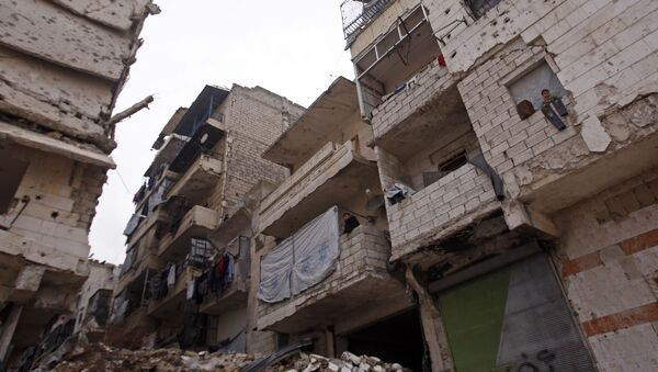 Residents in a government-held part of Aleppo's Salaheddin neighbourhood look out from the balconies of their damaged houses at the road on which the convoy evacuating civilians and rebel fighters from the last rebel-held neighbourhood in the northern Syrian city were supposed to pass - Sputnik International