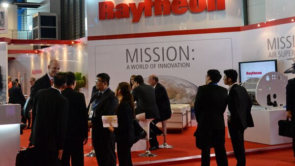 Trade visitors stand in front of a Raytheon booth during the Singapore Air Show. (File) - Sputnik International