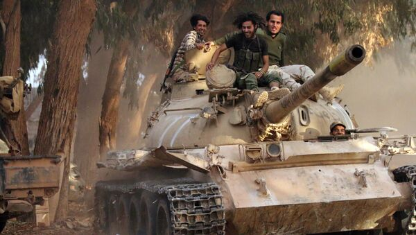 Soldiers from the Libyan National Army, led by Marshal Khalifa Haftar, drive their tank on November 19, 2016 in the Qawarsha sector, 10 kilometres (six miles) west of the centre of Benghazi, after they retook the area from jihadist fighters - Sputnik International