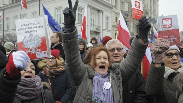 Protesters holding copies of Poland's constitution shout slogans during an anti-government demonstration, in Warsaw, Poland - Sputnik International