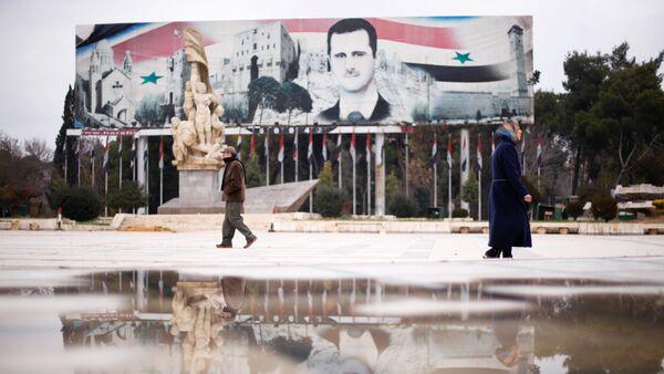 People walk past a billboard depicting Syria's President Bashar al-Assad at Saadallah al-Jabri Square, in the government controlled area of Aleppo, Syria December 17, 2016 - Sputnik International