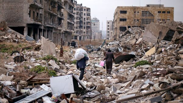 People walk amid the rubble as they carry belongings that they collected from their houses in the government controlled area of Aleppo, Syria December 17, 2016 - Sputnik International