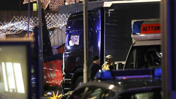 Police stand beside a damaged truck which ran into crowded Christmas market in Berlin, Germany. - Sputnik International