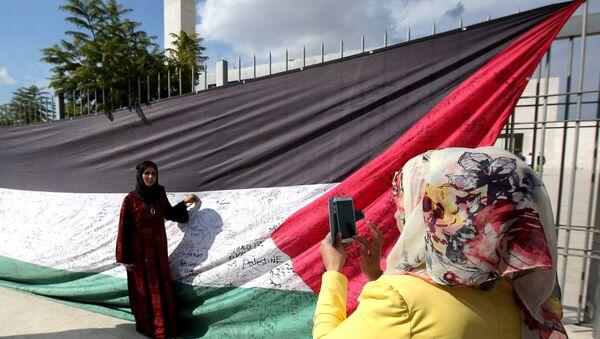 A Palestinian woman takes a picture of a 66-meter-long Palestinian flag - Sputnik International