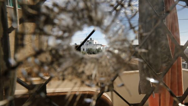 A nearby house is pictured through a bullet hole in a window inside a building that was the site of clashes between Jordanian police and Islamist militant gunmen in the village of Garifla, in Karak, Jordan, December 21, 2016 - Sputnik International
