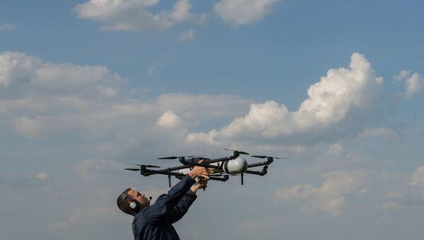 A man prepares to launch an unmanned aerial vehicles (UAV) during UAV demonstration flights. (File) - Sputnik International