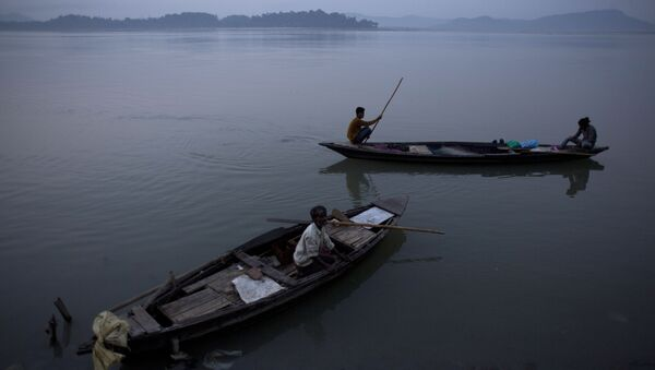 An Indian fisherman paddles a country boat as he leaves for fishing as another man sits in an anchored boat in the river Brahmaputra in Gauhati, India - Sputnik International