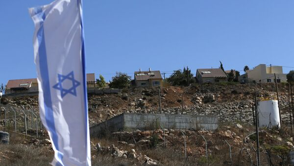 An Israeli national flag flying next to an Israeli building site with new housing units in the Jewish settlement of Shilo in the West Bank.  - Sputnik International