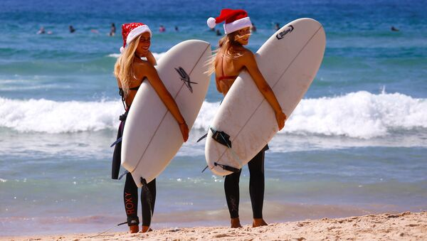German tourists Mimi Wiebeling (L) and Pauline Lapetite carry surfboards as they walk into the surf wearing Christmas hats at Sydney's Bondi Beach on Christmas Day in Australia - Sputnik International