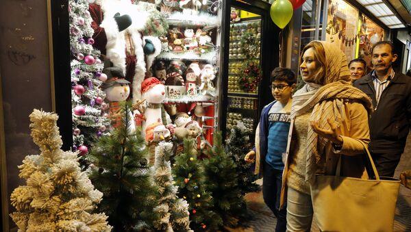 Iranians walk past Christmas decoration at a shop in the capital Tehran on December 24, 2016, on Christmas eve - Sputnik International