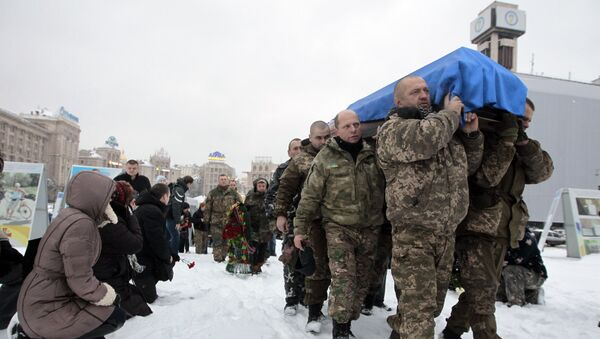 People, including servicemen and civilians, stand and kneel as the Ukrainian soldiers carry the coffin bearing the body of police captain Oleksandr Ilnitsky, who was shot dead by a sniper in the war conflict-hit Donetsk region, during a commemoration ceremony in Independence Square in Kiev, Ukraine, on Monday, Jan. 11, 2016 - Sputnik International