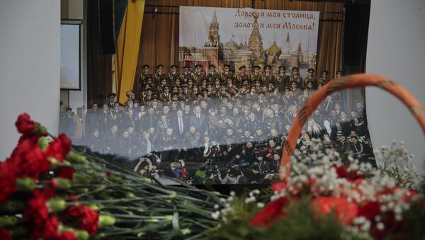 Flowers lay in front of a photo of a well-known military choir lays flowers at the military choir's building in Moscow, Russia, Sunday, Dec. 25, 2016, after a plane carrying 64 members of the Alexandrov Ensemble, crashed into the Black Sea minutes after taking off from the resort city of Sochi - Sputnik International
