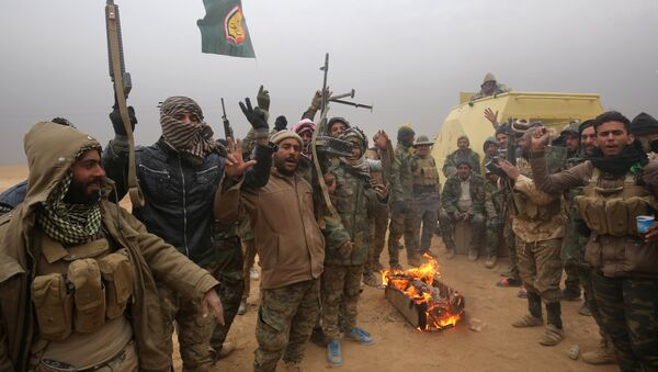 Iraqi Shiite fighters from the Hashed al-Shaabi (Popular Mobilisation) paramilitaries gesture to the camera as they warm up around a fire near the village of Tal Faris, south of Tal Afar, on November 30, 2016, during a broad offencive by Iraq forces to retake the city Mosul from jihadists of the Islamic State group - Sputnik International