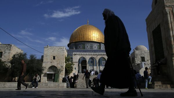 A Palestinian man walks past the Dome of Rock at the Al-Aqsa Mosque compound after the Friday prayer in Jerusalem's Old City on November 11, 2016 - Sputnik International