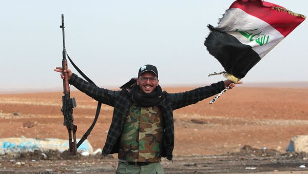 An Iraqi forces member flashes his gun as he waves his national flag in the village of Arabat, south of Mosul, as temperatures continue to drop, on December 1, 2016 - Sputnik International