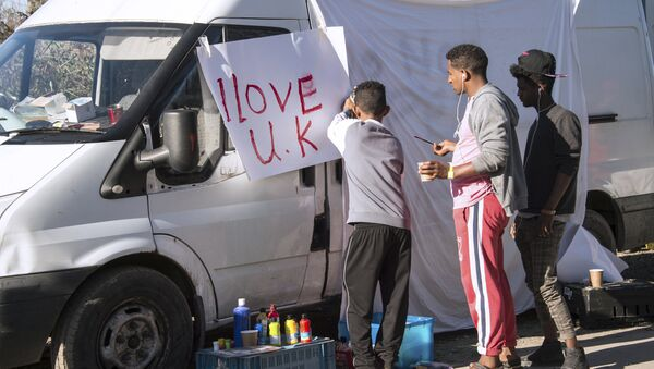 Young migrants paint a sheet of paper with the lettering 'I love UK' in the 'Jungle' migrant camp, in Calais, northern France, on October 31, 2016, during a massive operation to clear the squalid settlement where 6,000-8,000 people have been living in dire conditions. - Sputnik International