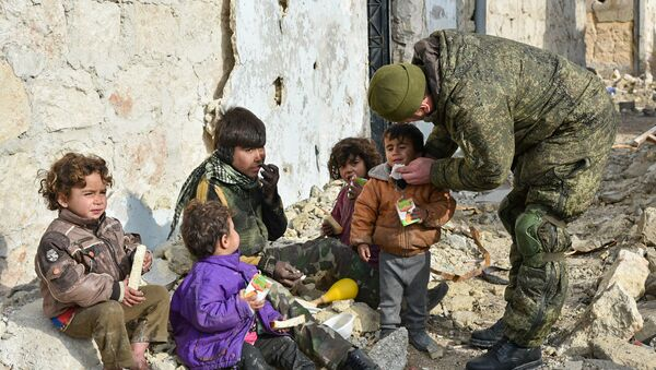 Military engineers of the Russian Army's international counter-mine center are seen in an Aleppo street with children. File photo - Sputnik International