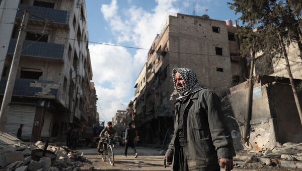 Syrian Abu Khaled looks at the rubble of his destroyed house in the rebel-held town of Douma, on the eastern outskirts of Damascus, on December 30, 2016, on the first day of a nationwide truce - Sputnik International