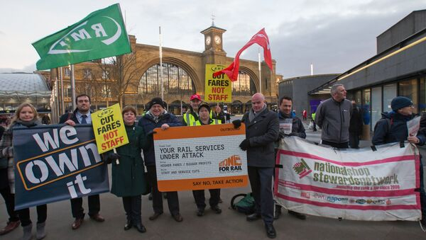 Protestors hold placards as they demostrate against the annual rise in rail tickets, for travel on trains, outside King's Cross railway station in London on January 3, 2017 - Sputnik International