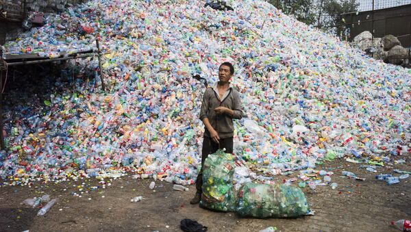 Chinese labourer sorting out plastic bottles for recycling in Dong Xiao Kou village, on the outskirt of Beijing (File) - Sputnik International