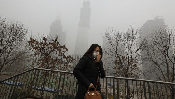 A woman wearing a mask for protection against air pollution walks on a pedestrian overhead bridge in Beijing as the capital of China is shrouded by heavy smog on Tuesday, Dec. 20, 2016 - Sputnik International